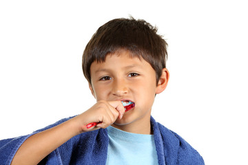 Young boy brushing teeth on white background