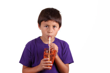 Young boy drinking from orange glass on white background