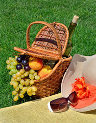 Beach hat, sun glasses, picnic basket with fruits and  bottle of