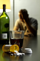 Depressed man with wine and prescription medication, vertical