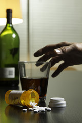 Hand reaching for wine and prescription pills, vertical