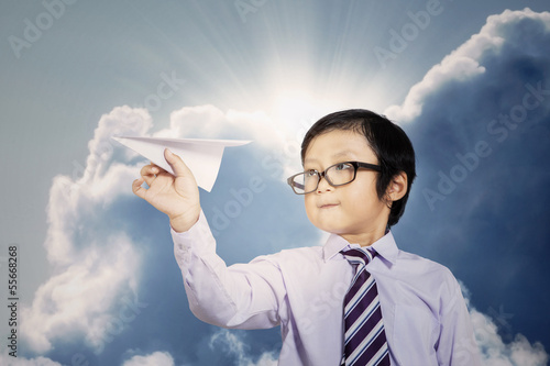 Little businessman with paper plane outdoor