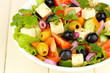 Fresh salad in plate on wooden table