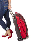 Woman in Capri Blue Jeans Pulling a Red Travel Luggage