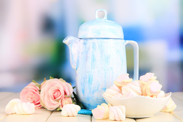 Antique white teapot on wooden table on room background