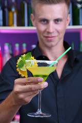 Portrait of handsome barman preparing cocktail, at bar