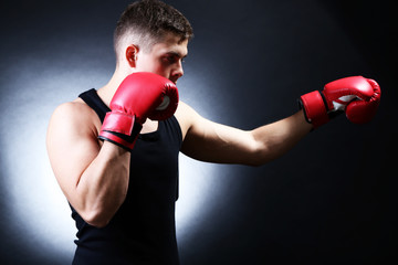 Handsome young muscular boxer on dark background