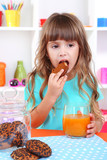 Little girl eating cookies and drinking juice sitting at table