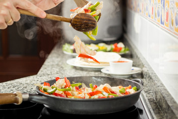 Closeup of man cooking vegetables and chicken in a pan