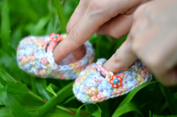 Woman fingers playing baby shoes on the garden