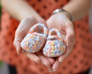 Woman holding cute wollen baby shoes