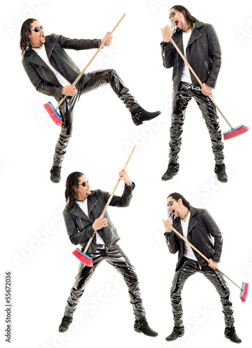 Caucasian man playing broom like guitar against white