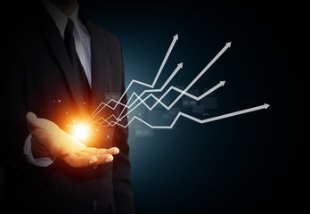 Hand holding a rising arrow, representing business growth.