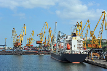 Lumber stack, ship ans train under crane bridge