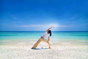 asian female performing yoga on a beach
