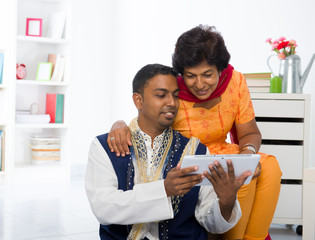 indian mother and son enjoying surfing with tablet in the living