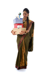 Portrait of a woman in traditional saree holding gifts and smili