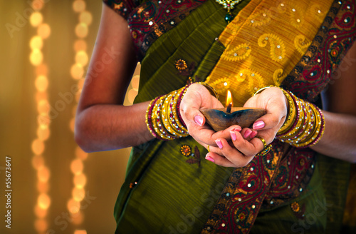 diwali or deepavali photo with female holding oil lamp during fe