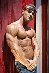 Muscular male bodybuilder against beach changing room