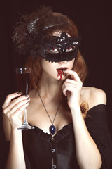 Redhead vampire woman in mask with glass of blood.