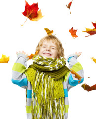 Child in woolen scarf playing with  maple leaves