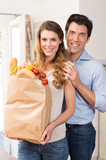 Couple With Grocery Bag In Kitchen
