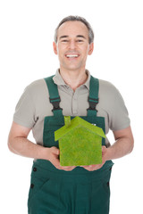 Happy man holding house covered with grass
