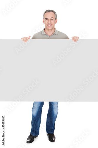 Happy Mature Man Standing Behind Placard