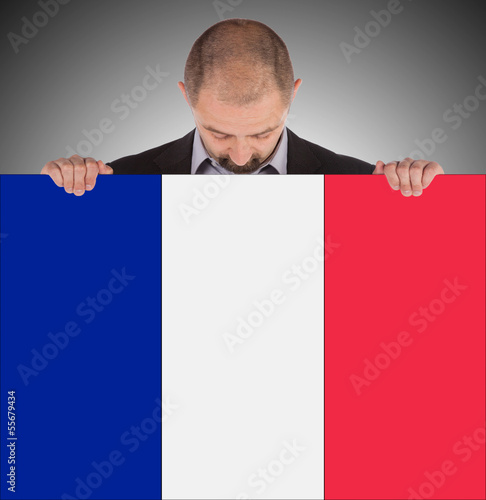 Smiling businessman holding a big card, flag of France