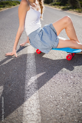Body of young woman sitting on her skateboard
