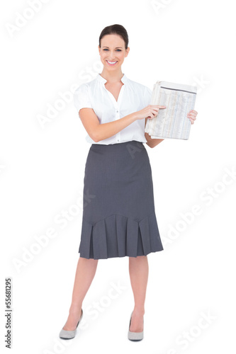 Happy classy businesswoman holding newspaper