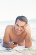 Smiling handsome man on the beach holding his cellphone