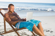 Handsome man using his laptop while relaxing on his deck chair