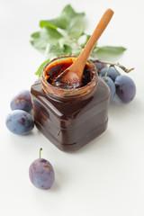 Plums beside open jar of plum jam