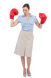 Attractive businesswoman posing with boxing gloves