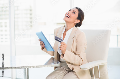Laughing businesswoman shopping online with tablet pc