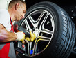 Motor mechanic is fitting a tyre with new alu rim