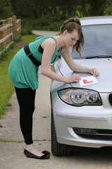 Learner driver putting her L plate on bonnet of  car