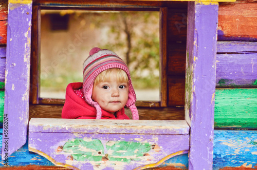baby girl in wooden house