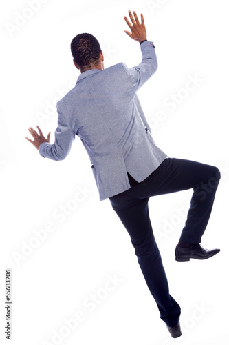 Young businessman climbing a wall, isolated over a white backgro