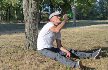 Alcoholic sitting drinking in a park