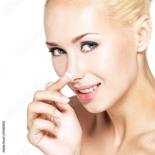 Woman applying cosmetic  cream on the nose