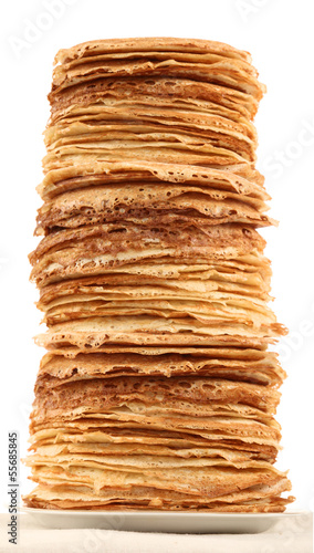 Very high pile of pancakes on plate