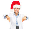 Smiling doctor woman in santa hat pointing down on copy space