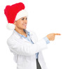 Smiling doctor woman in santa hat pointing on copy space