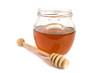 Honey dipper next to a jar of honey