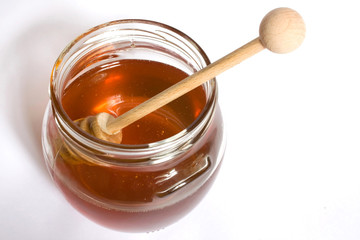 Honey dipper in a jar of honey close up