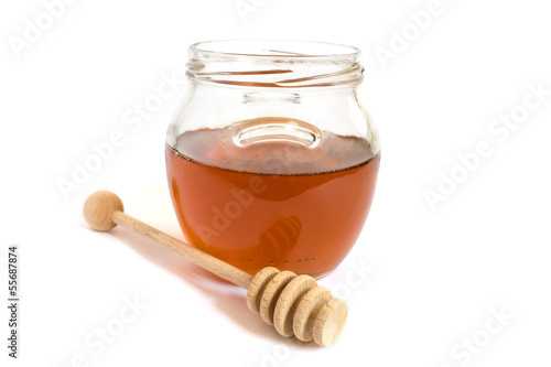 Honey dipper next to a jar of honey