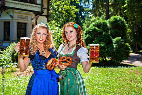 Two girls with Oktoberfest beer stein and pretzel