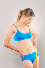 Slim blond girl measuring her waistline with tape.